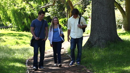 Three students talking to each other as they walk on a park trail