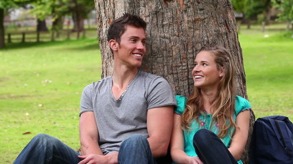 Two friends smiling as they look at each other while sitting against a tree