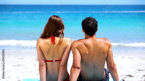Couple sitting together on the sand