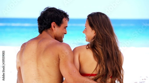 Smiling couple sitting while embracing