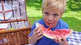 Boy eating a watermelon and smiling