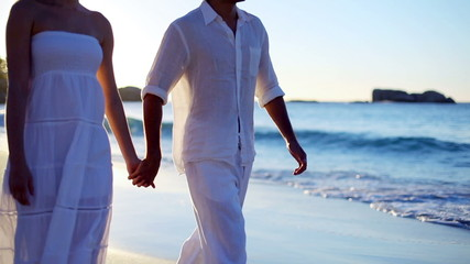 Couple holding hands while they walk along the beach