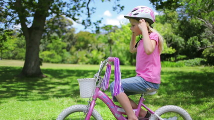 Girl puts on a cycling helmet and holds the handle bars