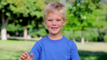 Boy waving towards the camera while smiling