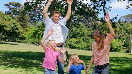 Family jumping up and down with their arms raised
