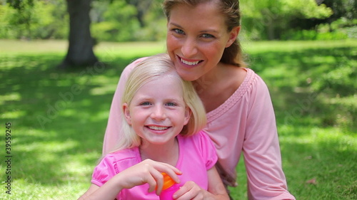 Girl blowing bubbles with her mother