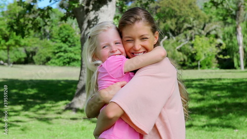 Woman hugging her daughter tightly