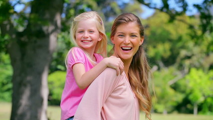 Woman lifts her daughter into a piggy-back before smiling