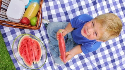 Overhead shot of a boy sitting on a picnic blanket while eating a slice of watermelon and smiling
