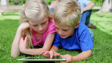 Brother and sister using a tablet pc together while lying