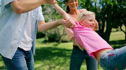 Girl being swung back and forth by his parents who are holding her arms