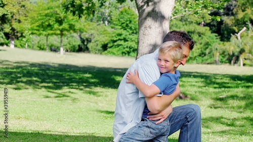 Father kneels on the grass before hugging his son