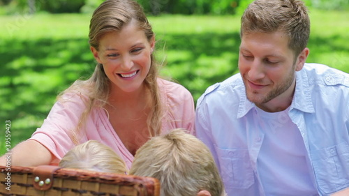 Two children reach into a picnic basket while sitting