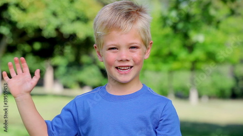 Boy smiling and waving before giving the thumbs up