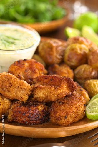 Breaded fried calamary with baked potatoes and tzatziki