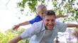 A father sways from side to side while giving his son a piggy back with his arms spread