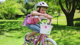 A girl sits on a bike while leaning on the handlebars