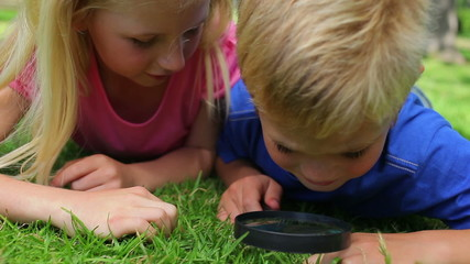 Two children searching through grass with a magnifying