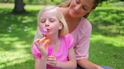 A girl repeatedly blows bubbles with her mother as she sits in the park