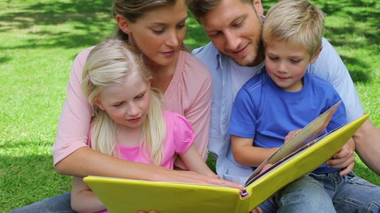 A family turning the page of a book and then continuing to read before smiling towards the camera