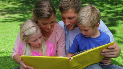 Family reading a book while sitting together before looking at
