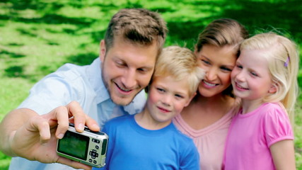 Father takes a picture of himself and his family before looking