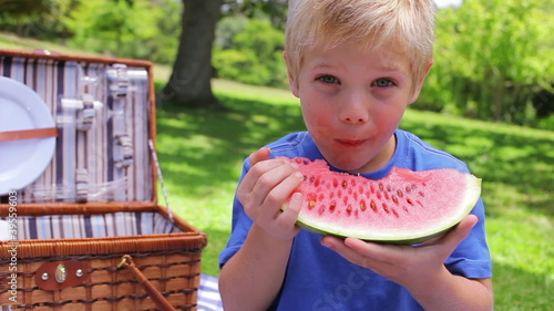 A boy looks at the camera while biting a watermelon
