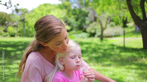 A woman sits with her daughter who is blowing a dandelion