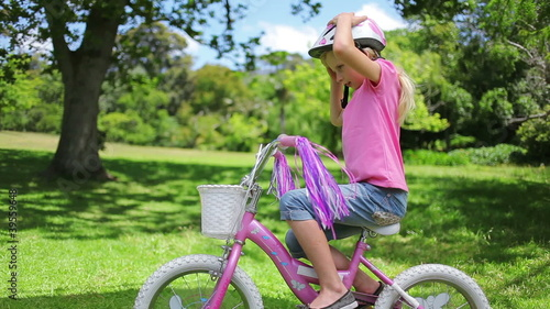 A girl picks her helmet out of a bike basket and puts it