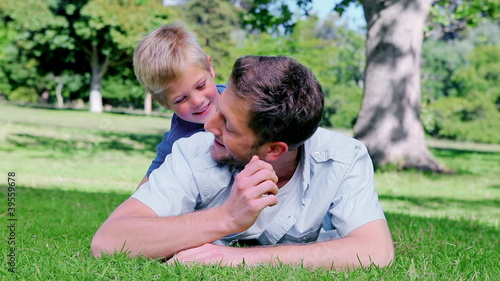 Father looking ahead while lying on the grass before his son