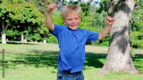 Boy jumps around and spinning with his arms spread before stopping and looking at the camera