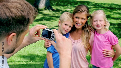 A man takes a photo of his family who are embracing