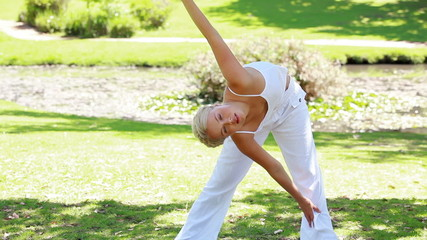 Woman holds an aerobics position as she smiles