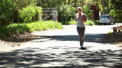 Jogging woman runs down the street with the camera in front