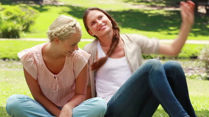 Woman sitting as her friend sits down with her as they then talk and look to the side