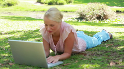 The camera shifts focus from the park to a woman on her laptop