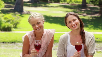 Two friends enjoying wine as they both smile and look