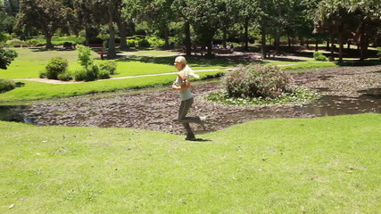 A woman runs in the park as the camera follows her