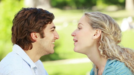 A couple look at each other as they kiss in the park