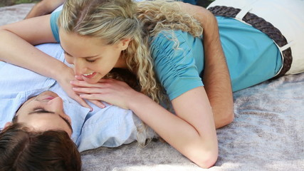 A man lies on the ground as his girlfriend lies down on his