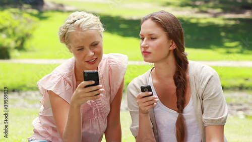 Two women with their phones in hand in the park