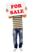 Young casual man holding sale sign against white background