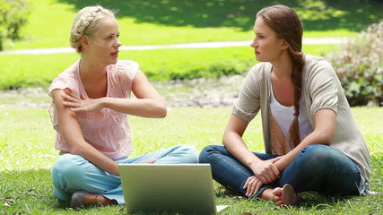 A pair of girls look at a laptop and then talk to one another