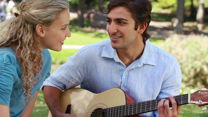 A boyfriend plays guitar for his girlfriend as they look at each other