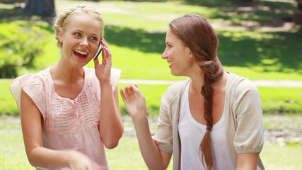 Two girls sit in the park and pass the phone back and forth