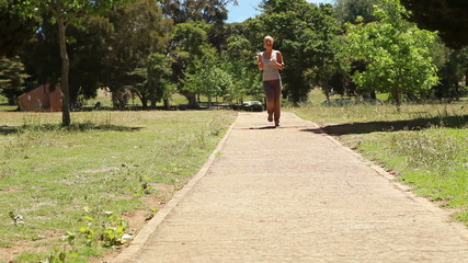 A woman jogs up a footpath towards and past the camera