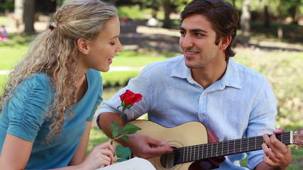 A man serenades his girlfriend with a song as she holds a rose as they look at the camera