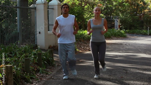 A jogging couple run together down the street