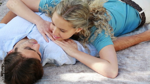 A woman lying on her boyfriend talk as they smile