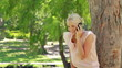 A woman standing by a tree talking on her phone as she hangs up at looks at the camera
